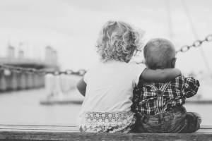 siblings hugging each other sitting on a dock