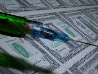 syringe with a vaccine and money