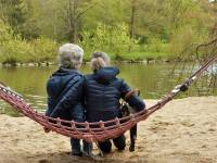 mom and her daughter sitting on a hamock looking at birds on a lake